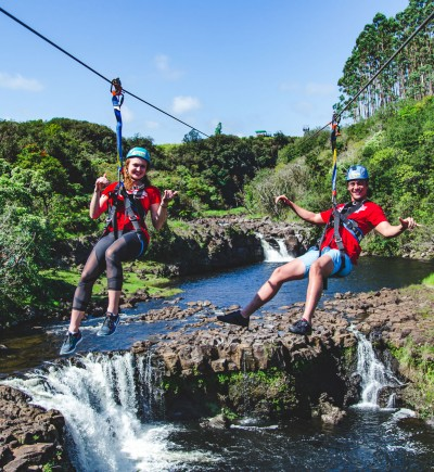 Woman and man ziplining over Umauma river